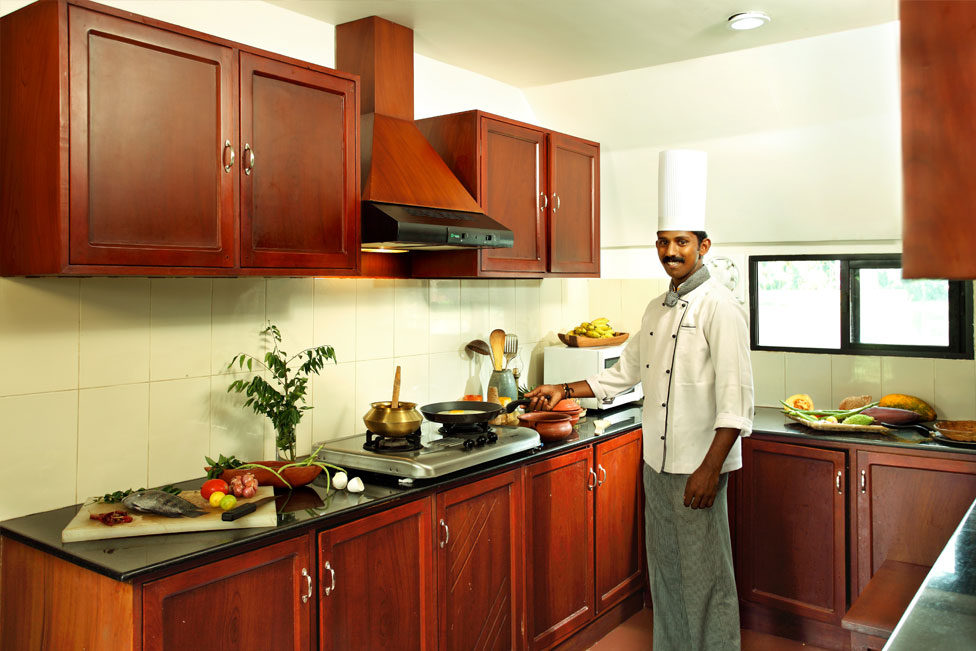 Chef cooking in the houseboat kitchen Kerala India;