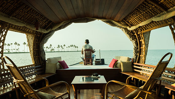 Living room on the houseboat with lounge chairs and boatman Kerala India